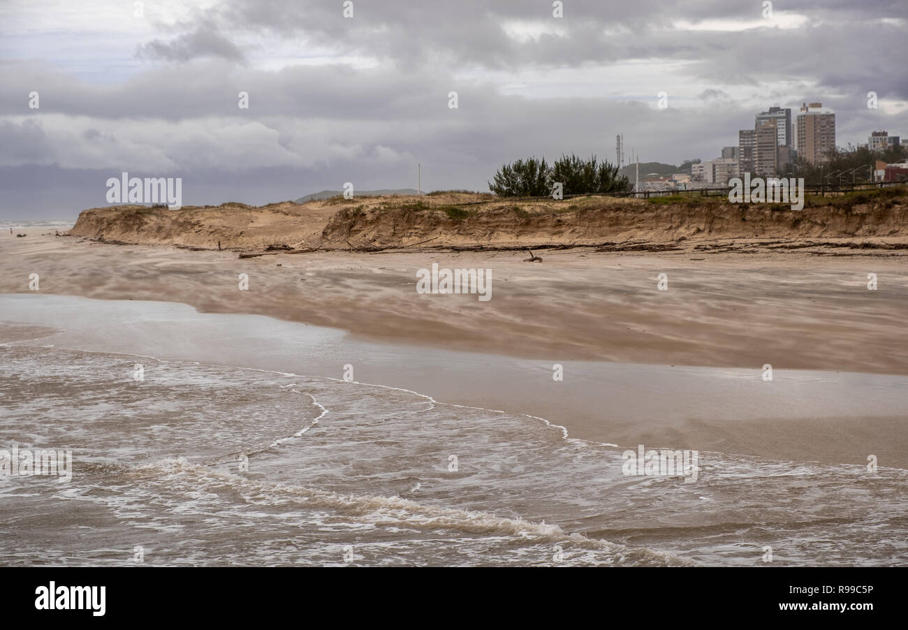 View of the beach on a very windy day in the winter season. City downtown in the background. Torres beach, Rio Grande do Sul state, Brazil. - Stock Image