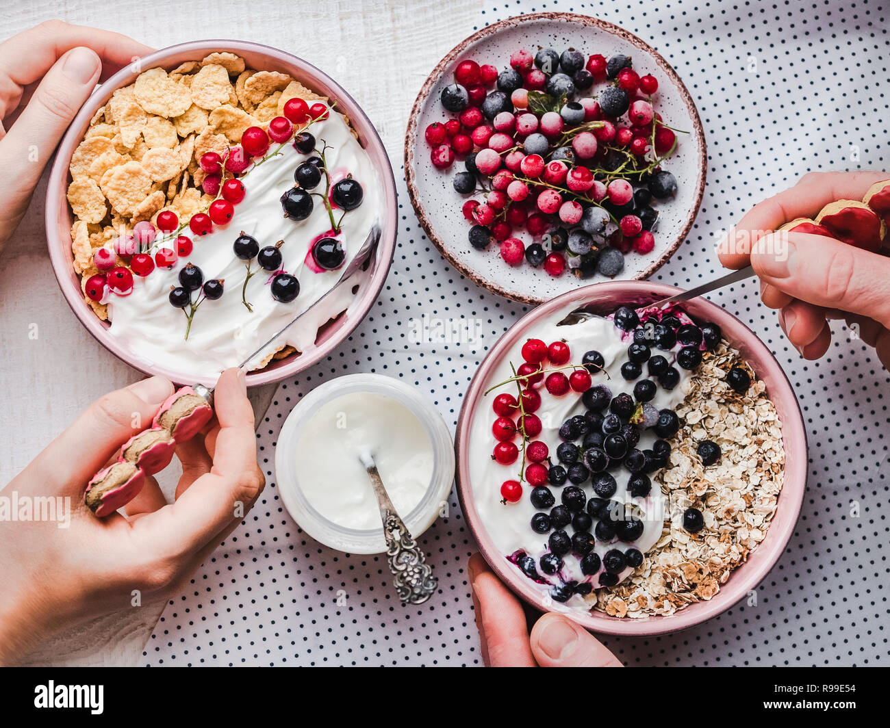 Festive and healthy breakfast for loved ones. Vintage bowls, cornflakes, granola, yogurt, fresh berries and hands of a young couple. Close-up, top vie Stock Photo