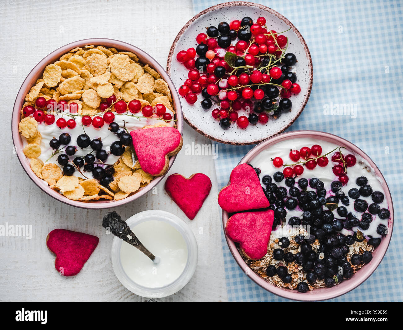 Festive and healthy breakfast for loved ones. Cereal biscuits in pink glaze, vintage bowls, cornflakes, granola, yogurt, fresh berries. Close-up, top  Stock Photo