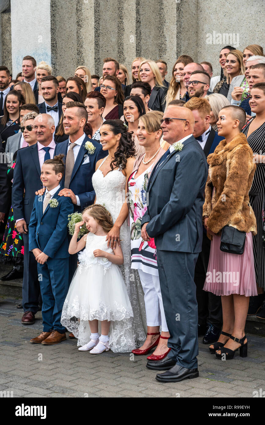 Wedding guests posing for a group photo outside the Akureyrarkirkja, Lutheran church in Akureyri, Iceland, Europe. - Stock Image