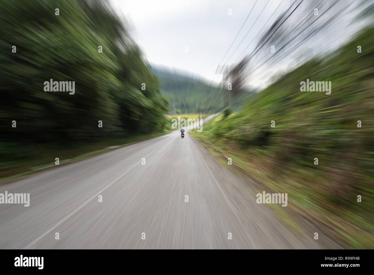 view from behind a scooter on a road in Laos with motion blur showing speed - Stock Image