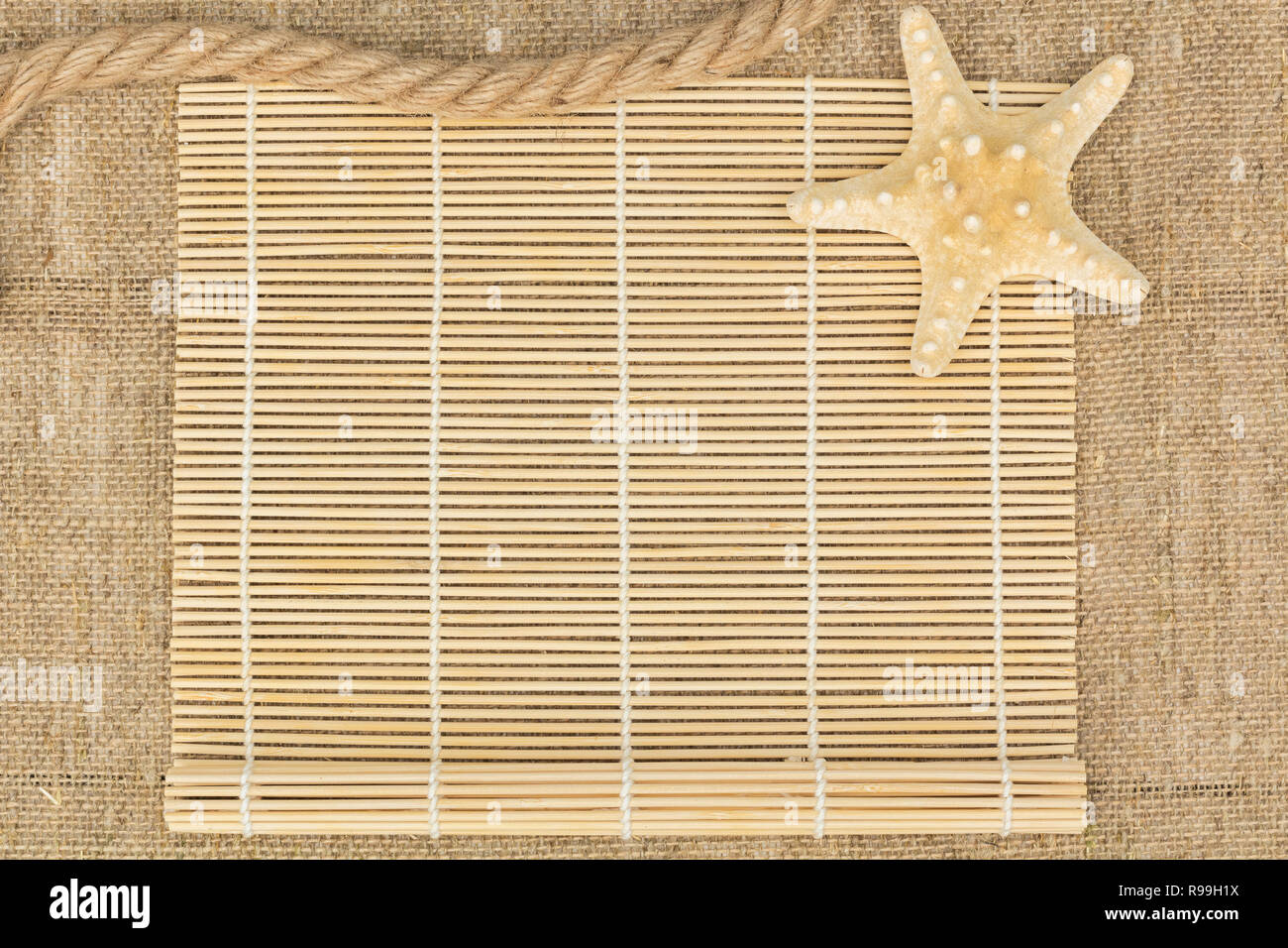 starfish and rope lying on a sackcloth - Stock Image