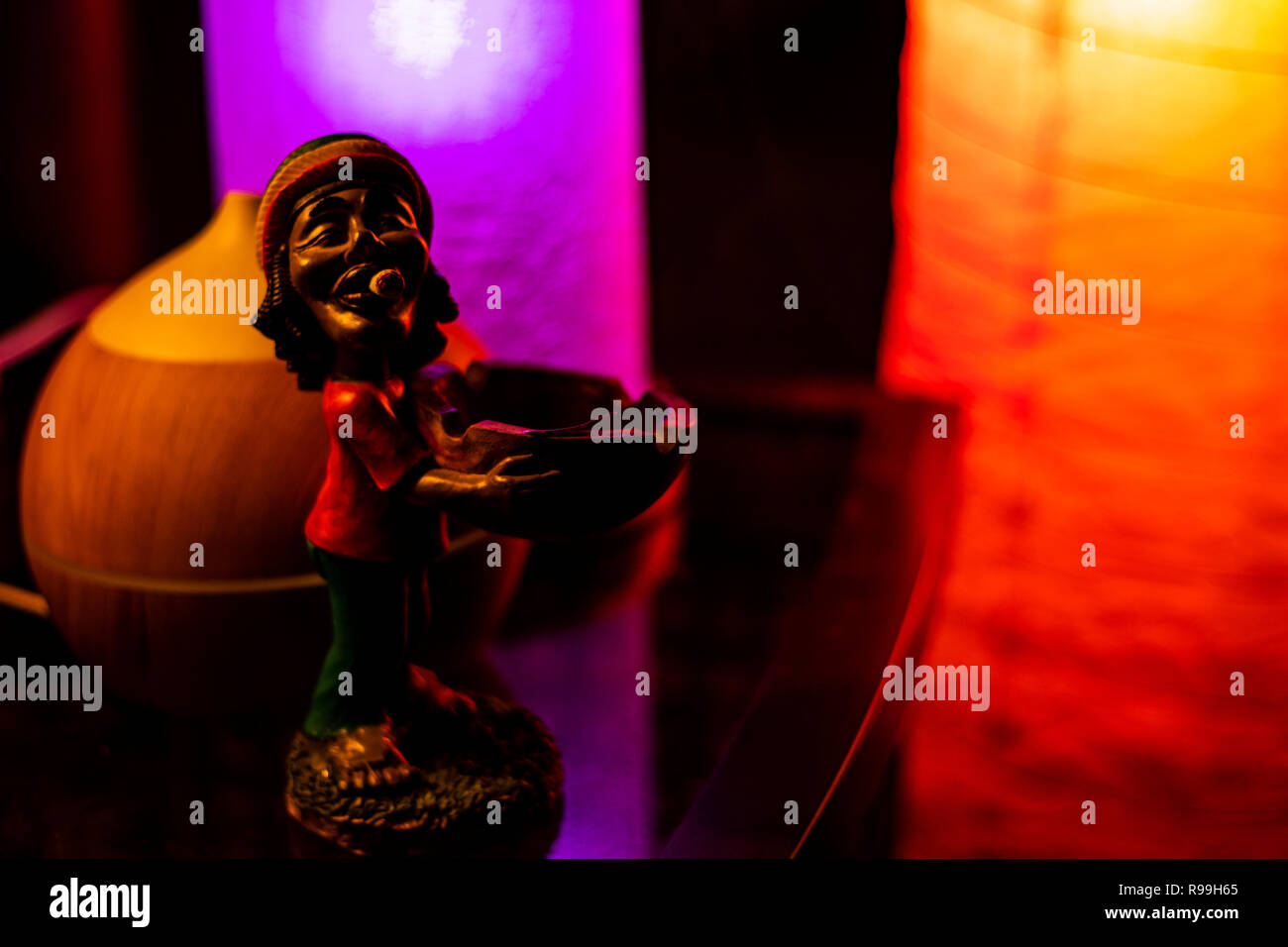 Bob Marley figurine on reflective glass desk by an oil diffuser lit by 2 led lamps. - Stock Image