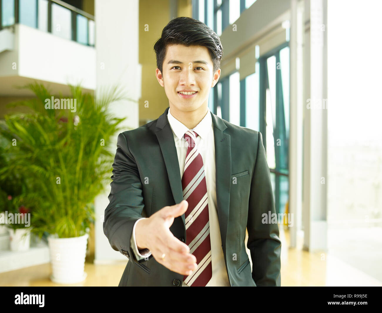 young asian corporate executive reaching out for a handshake, looking at camera smiling. - Stock Image