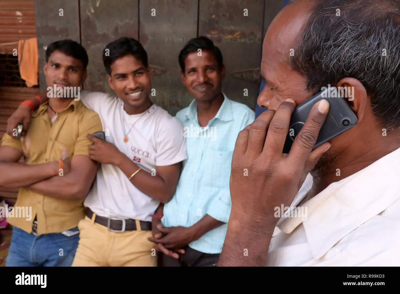 A mobile phone user in Mumbai, India, a migrant worker from Northern India, calling his family back home - Stock Image
