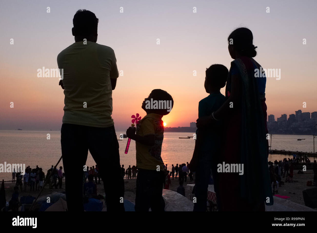 A nuclear family in Mumbai, India, including two children, enjoying the sunset at Marine Drive, a boulevard lining the Arabian Sea - Stock Image
