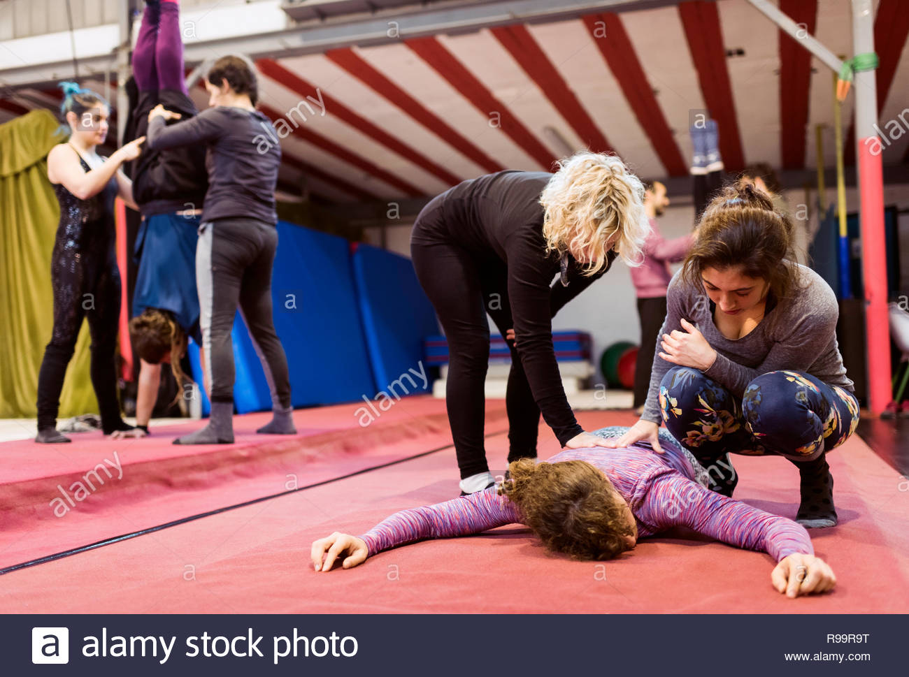 Female acrobats pressing on back of lying on floor woman with equilibrists training behind scenes on blurred background - Stock Image