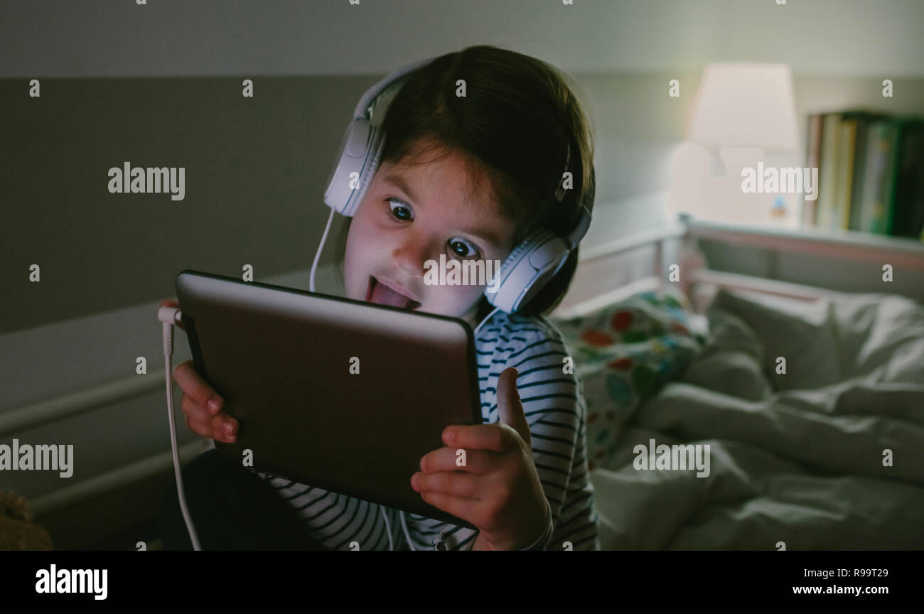 Funny girl grimacing with headphones looking at the tablet sitting on the bed at night - Stock Image