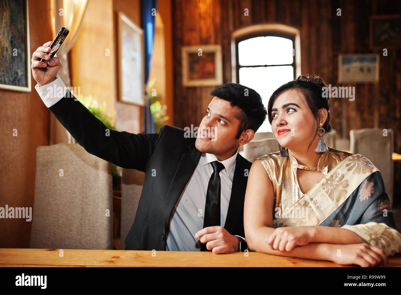 Elegant And Fashionable Indian Friends Couple Of Woman In Saree Man Suit Posed Indoor Cafe Making Selfie On Mobile Phone