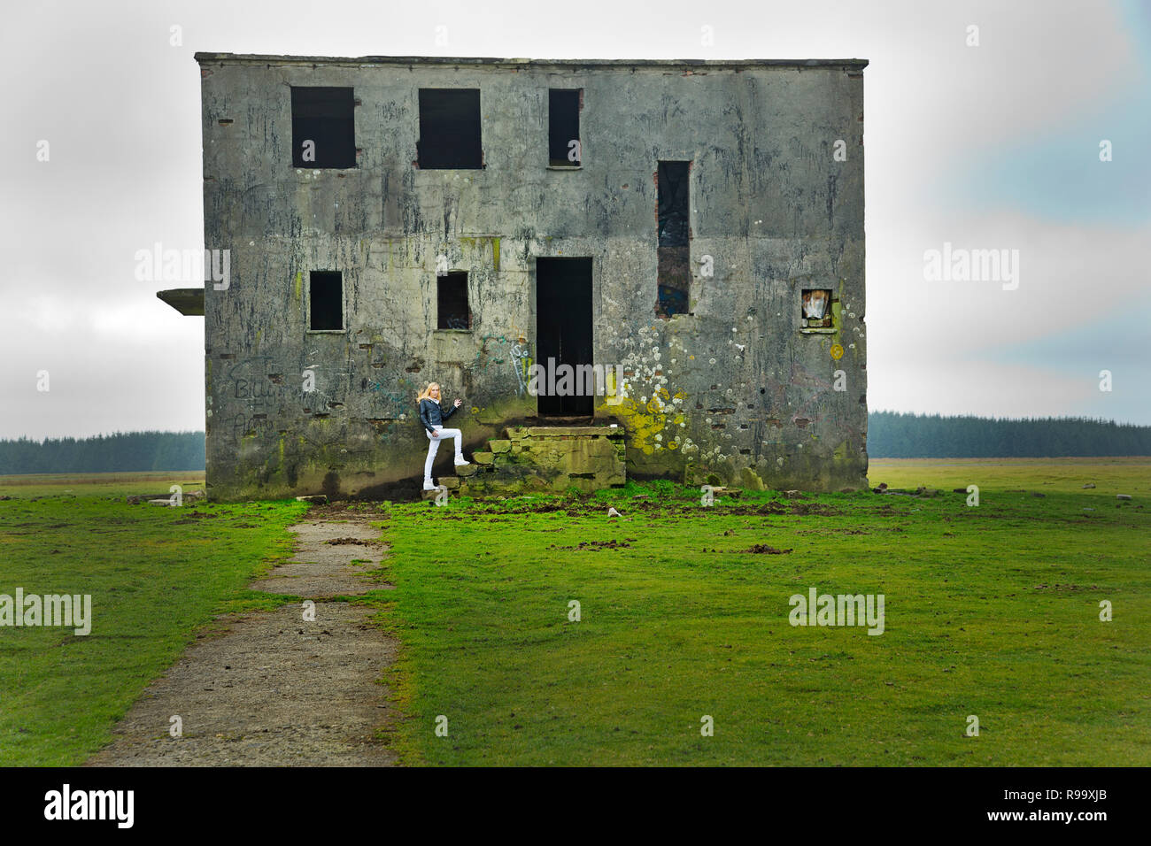 A young blond model entering an old disused building - Stock Image