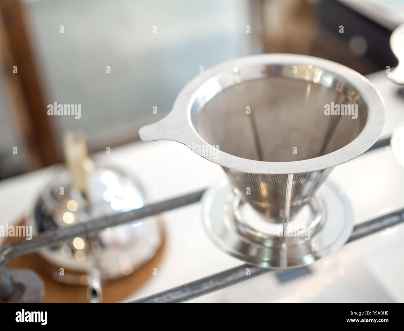 Stainless steel coffee filter reusable funnel coffee dripper, V-type filter cup with copy space. - Stock Image