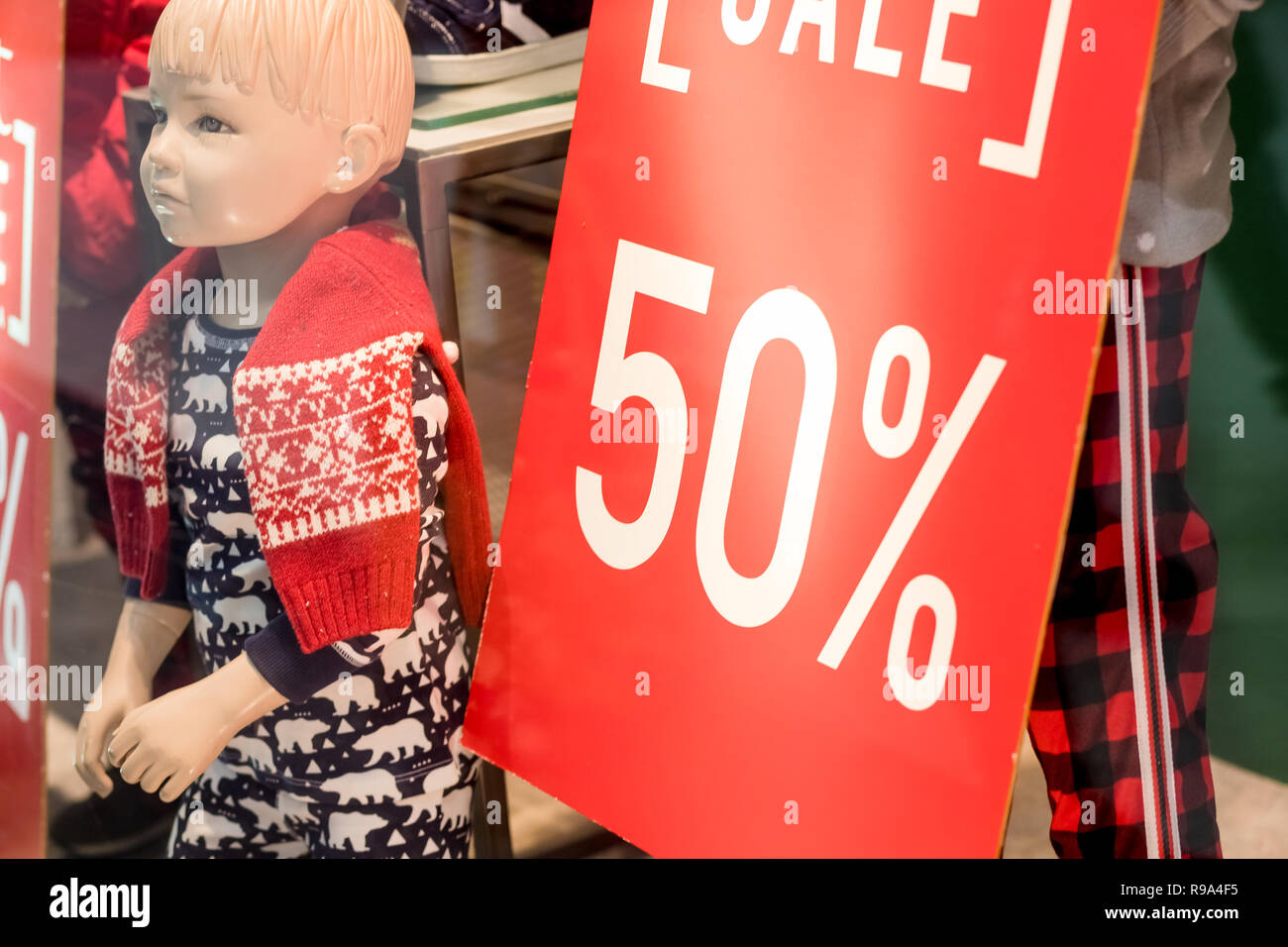 4b7d93c85335 red sale sign in kids clothes shop window next to a mannequin dressed in  winter clothes