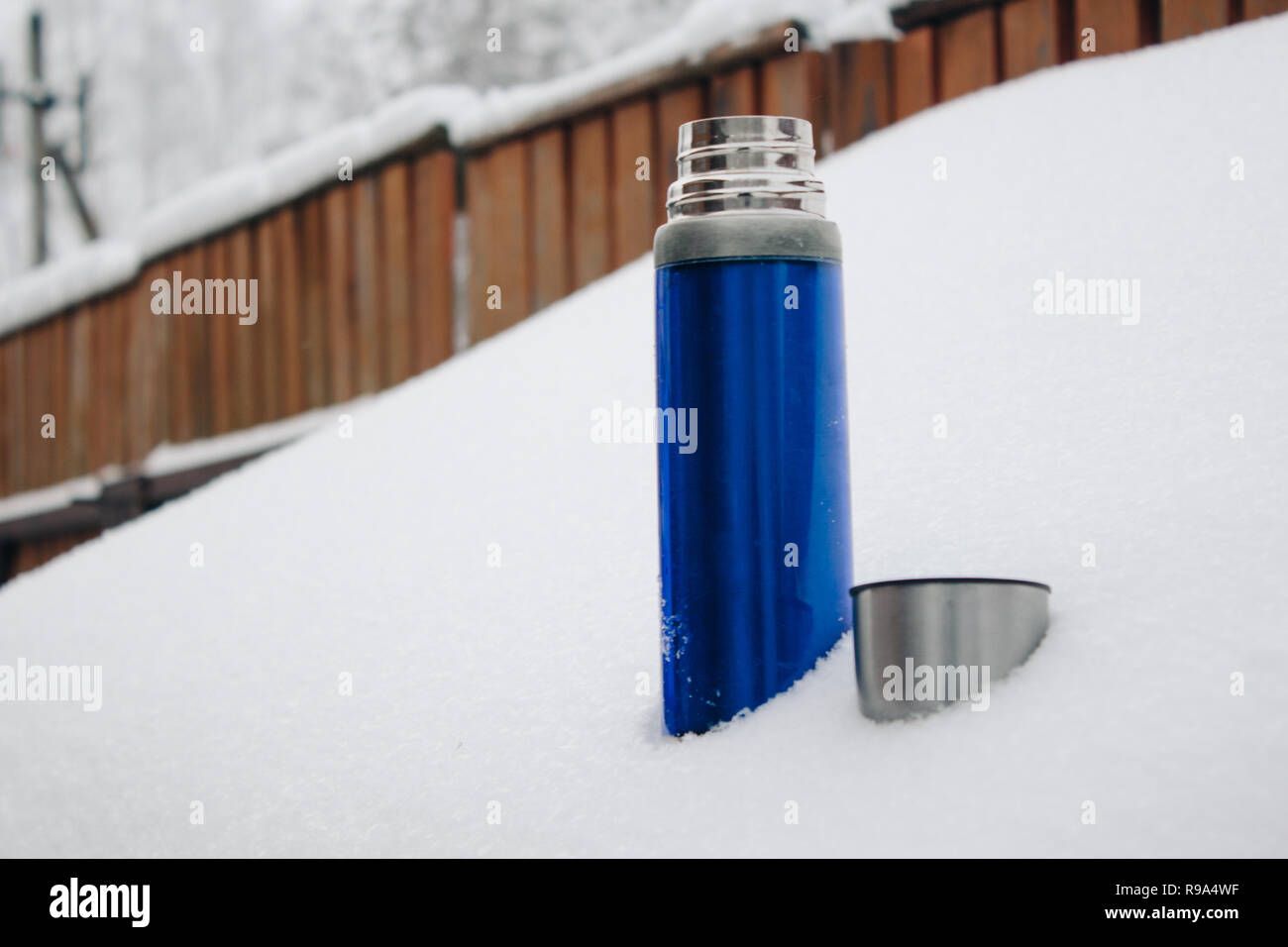 Close-up blue silver thermos with coffee or tea in snow, back yard. Winter holidays, hot drinks concept. - Stock Image