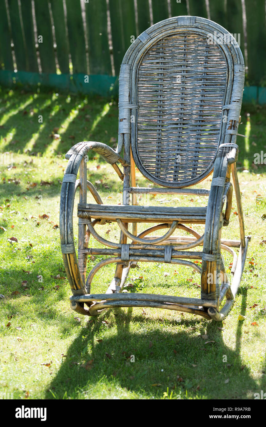 Old Wicker Rocking Chair In The Garden On The Grass Stock ...