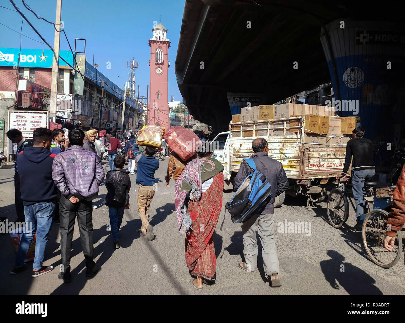 Ludhiana, Punjab, India. 21st Dec, 2018. Indian residents seen walking next to the city clock tower in Ludhiana city of Punjab, India. Punjab, a state bordering Pakistan, is the heart of India's Sikh community. The state is bordered by the Indian states of Jammu and Kashmir to the north, Himachal Pradesh to the east, Haryana to the south and southeast, Rajasthan to the southwest, and the Pakistani province of Punjab to the west. Punjab is primarily agriculture-based due to the presence of abundant water sources and fertile soils. The population of Punjab is estimated to be 30,452,879 - Stock Image