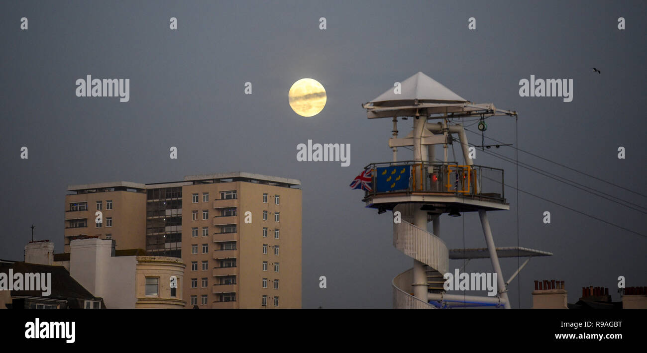 Brighton, Sussex, UK. 21st Dec 2018. A beautiful full moon rises above the zip wire ride on Brighton seafront this evening as the shortest day of the year comes to an end on the winter solstice Credit: Simon Dack/Alamy Live News  - Stock Image
