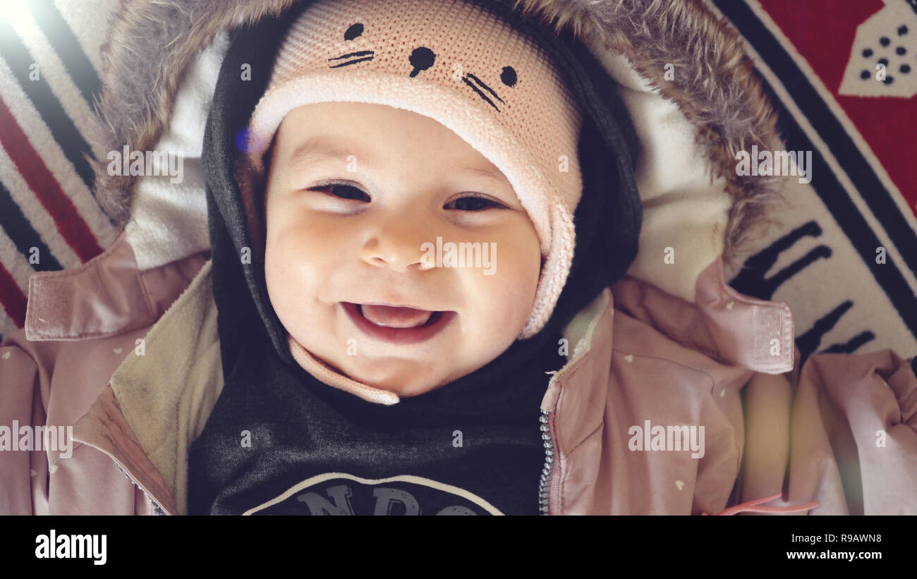 5372e67c4 Portrait of baby girl in winter jacket and hat smiling on christmas ...