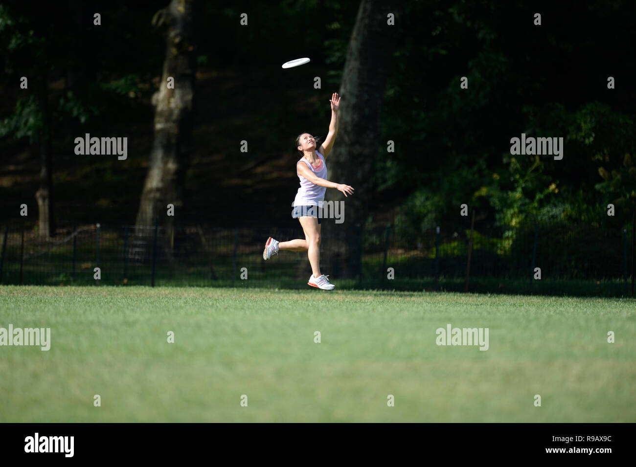 Girl playing frisbee in Central Park in New York City Stock Photo