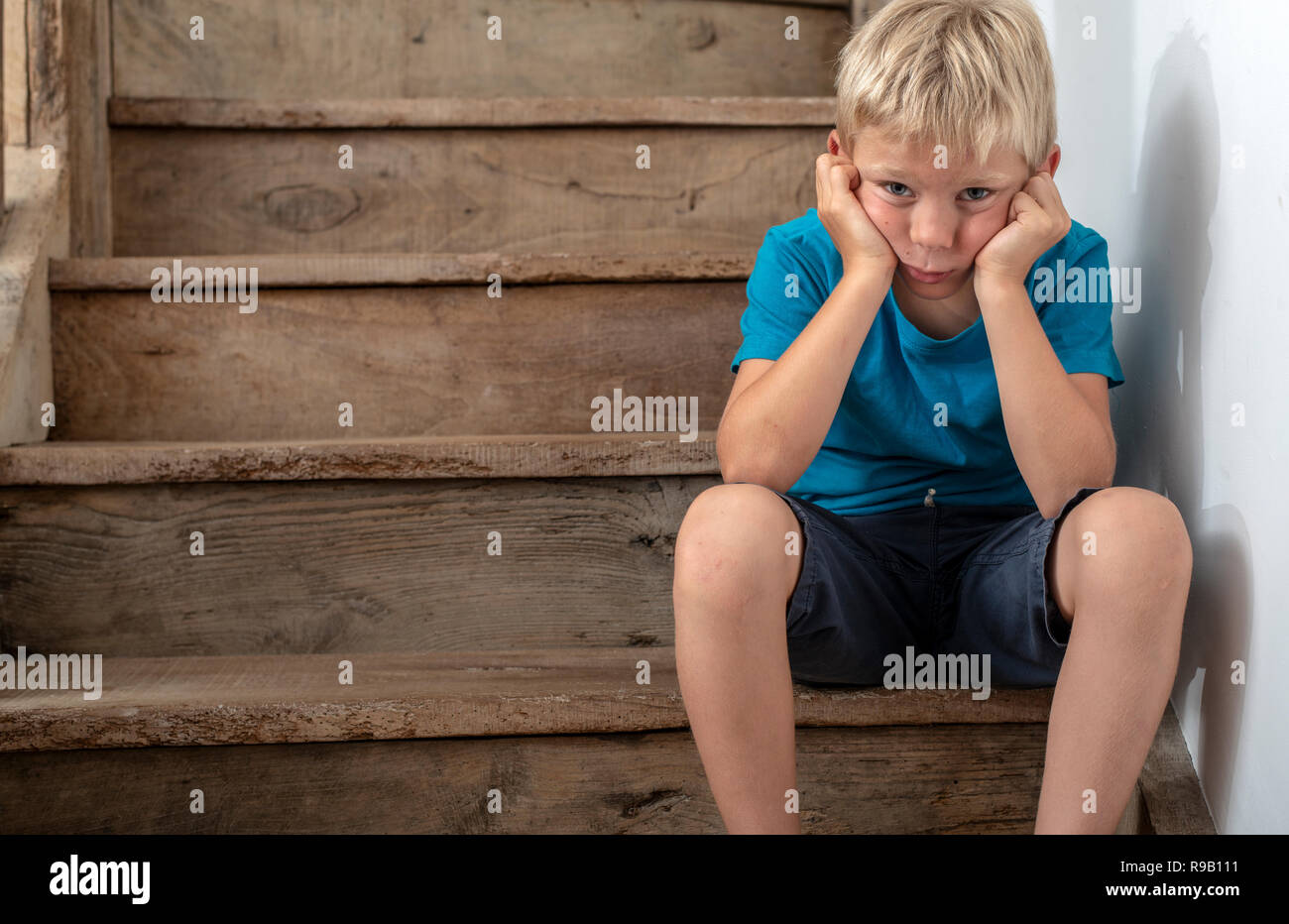Young kid sitting on stairs in naughty corner, angry or sad. - Stock Image