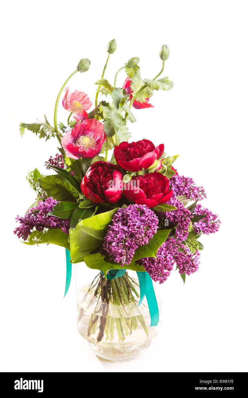 Large beautiful lush bouquet of flowers bright multicolored poppy, peony and lilac in a transparent vase on a white isolate background. - Stock Image
