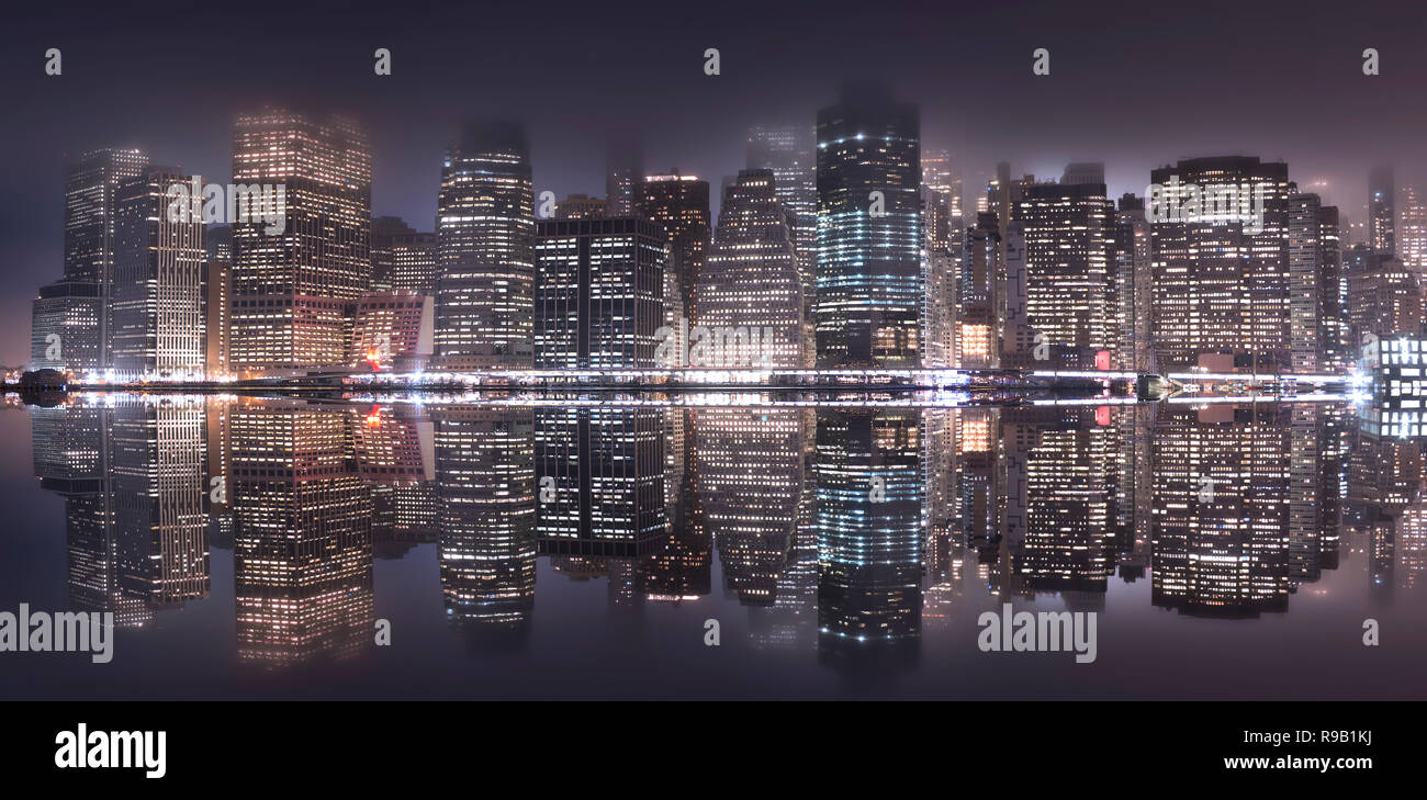 The Manhattan skyline reflects in the East River. Some of the best views of NYC are from Brooklyn Bridge Park. - Stock Image
