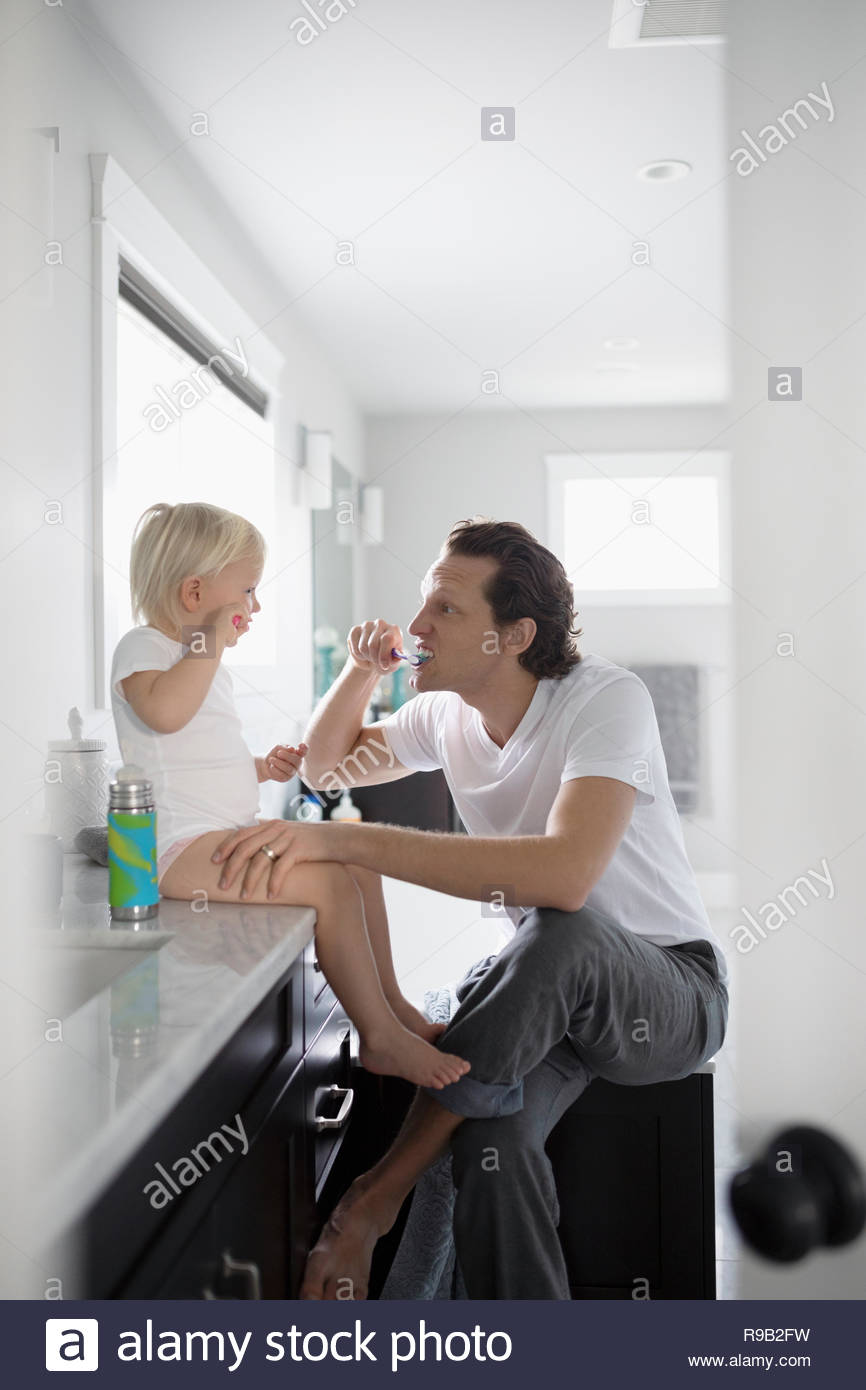Father teaching toddler daughter how to brush teeth in bathroom - Stock Image