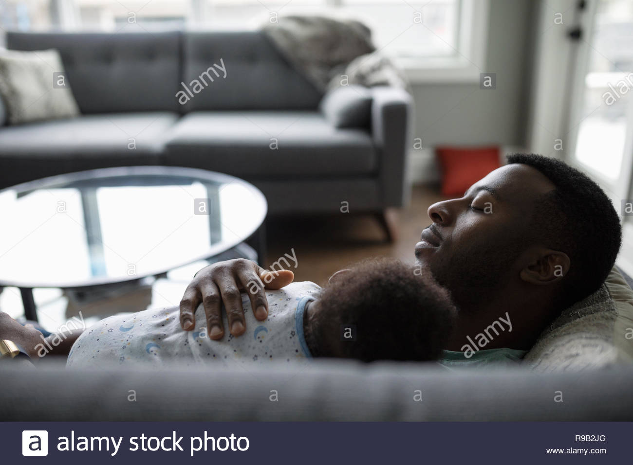 Tired father and baby son sleeping on living room sofa - Stock Image