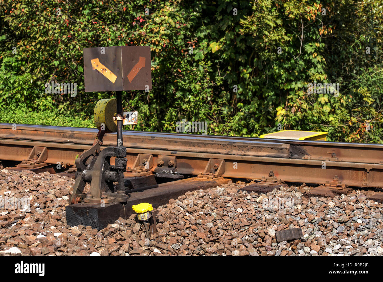 Old railway cross switch covered with black oil and dirt. Rail tracks and green bushes in background. - Stock Image