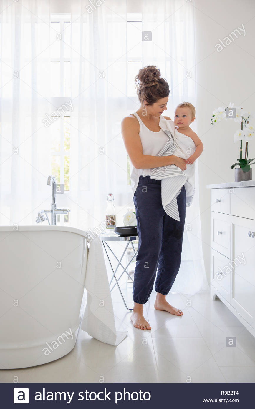 Mother holding baby daughter in towel after bath in bathroom - Stock Image