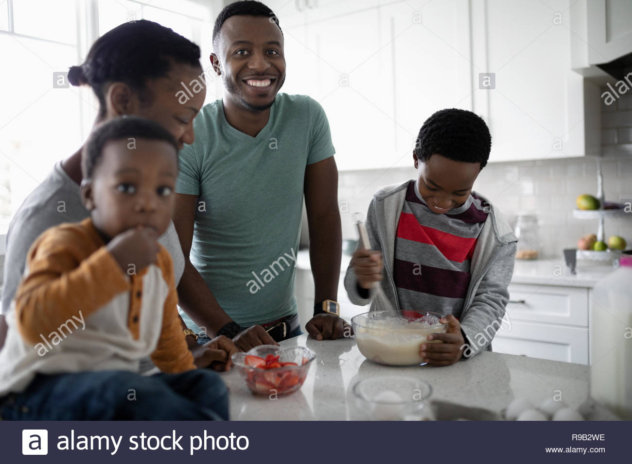 Portrait happy young family baking in kitchen - Stock Image