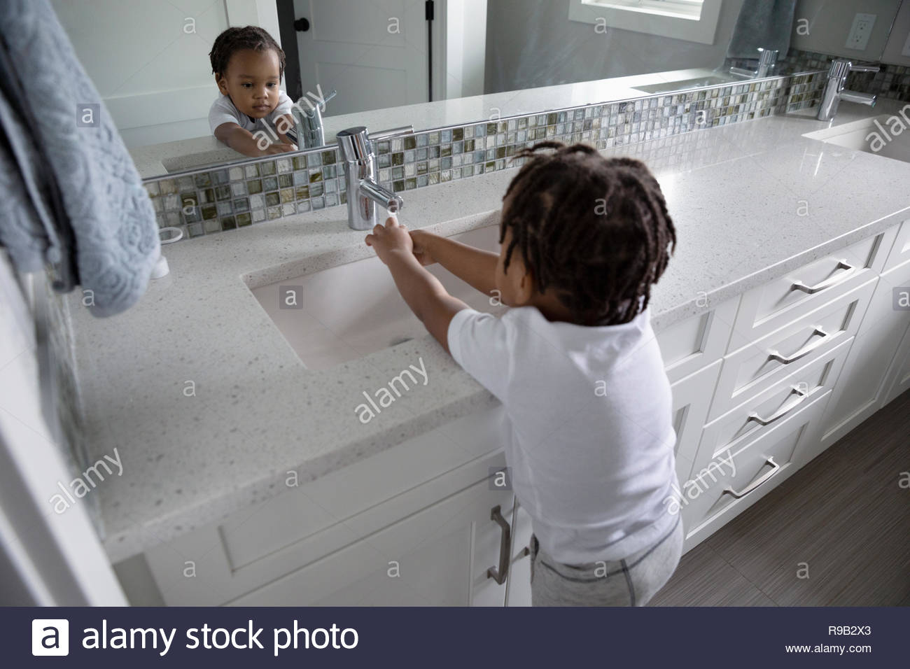 Toddler boy washing hands at bathroom sink - Stock Image