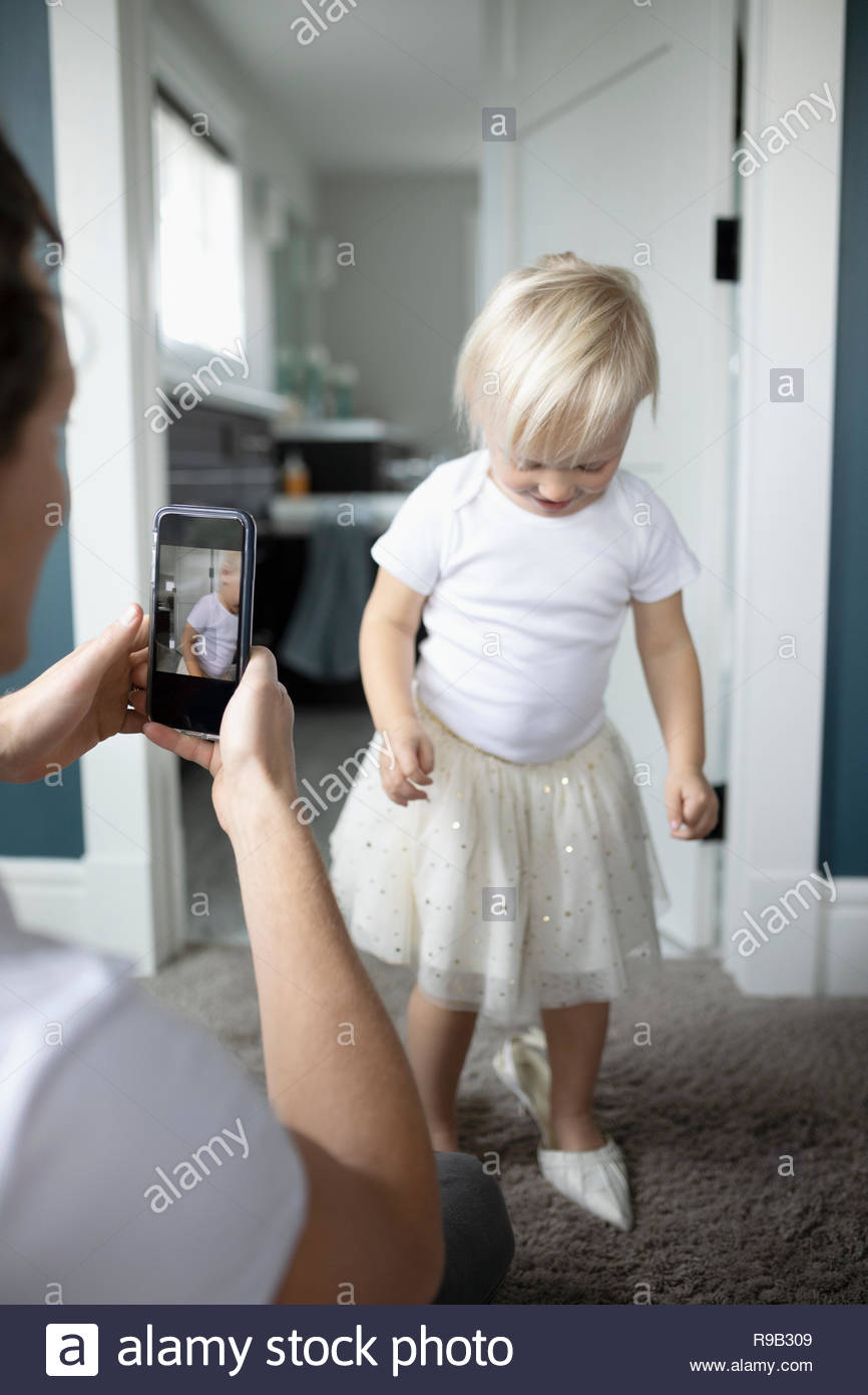 Father with camera phone photographing cute toddler daughter in high heels - Stock Image