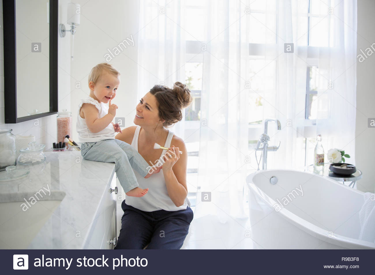 Mother and baby daughter in bathroom - Stock Image