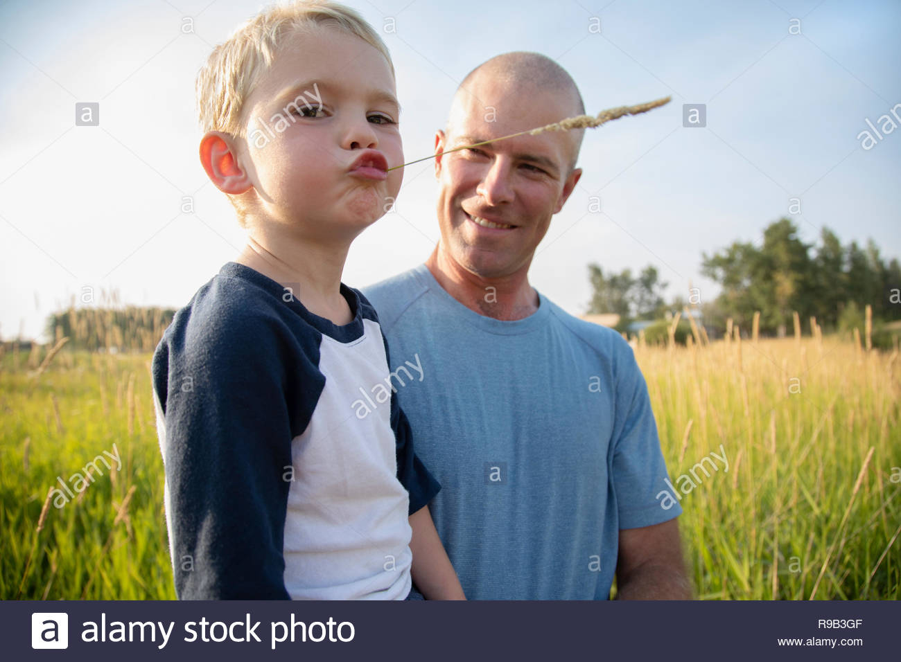 Portrait father holding son chewing on wheat stalk in rural field - Stock Image
