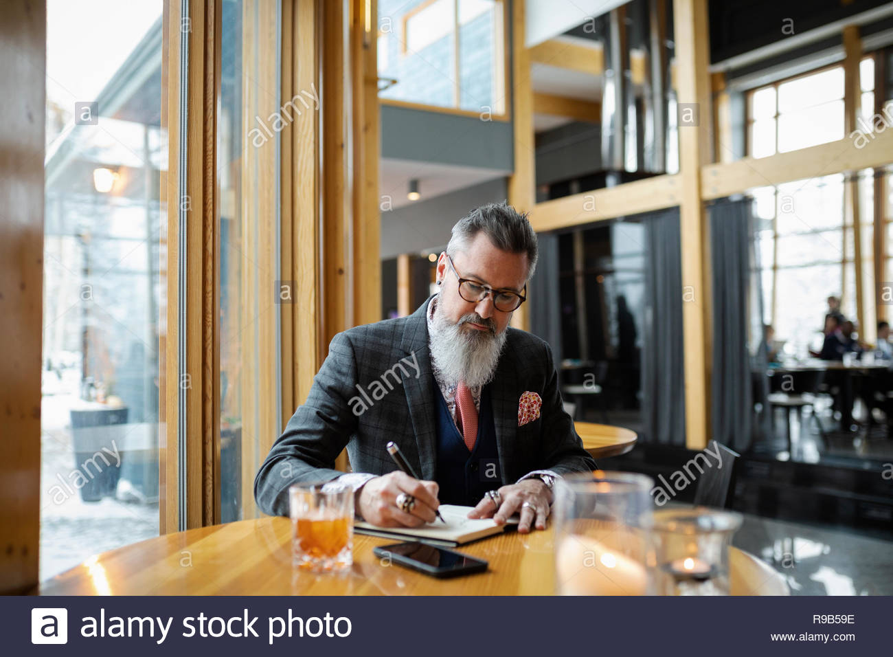 Fashionable hipster businessman with beard writing in notebook at restaurant table - Stock Image