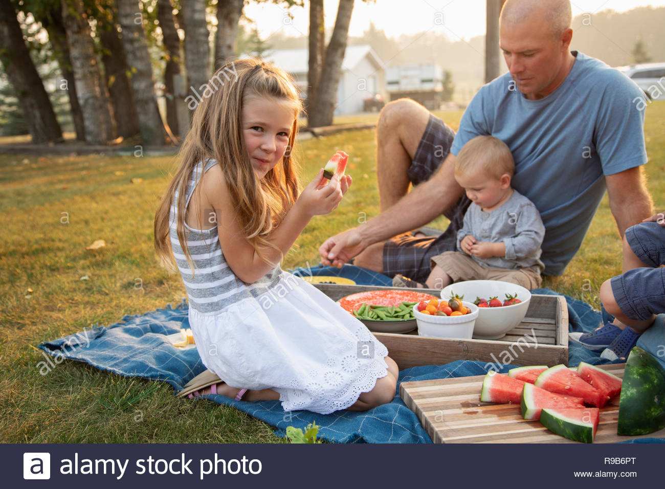 Portrait happy girl eating watermelon, enjoying picnic with family - Stock Image