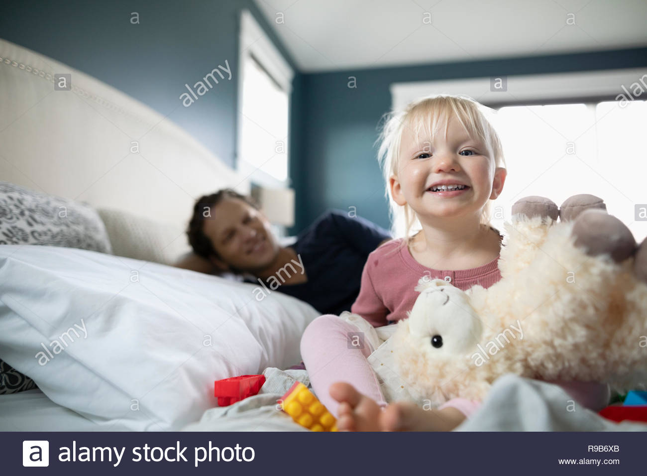 Portrait happy toddler girl playing with stuffed animal on bed Stock Photo