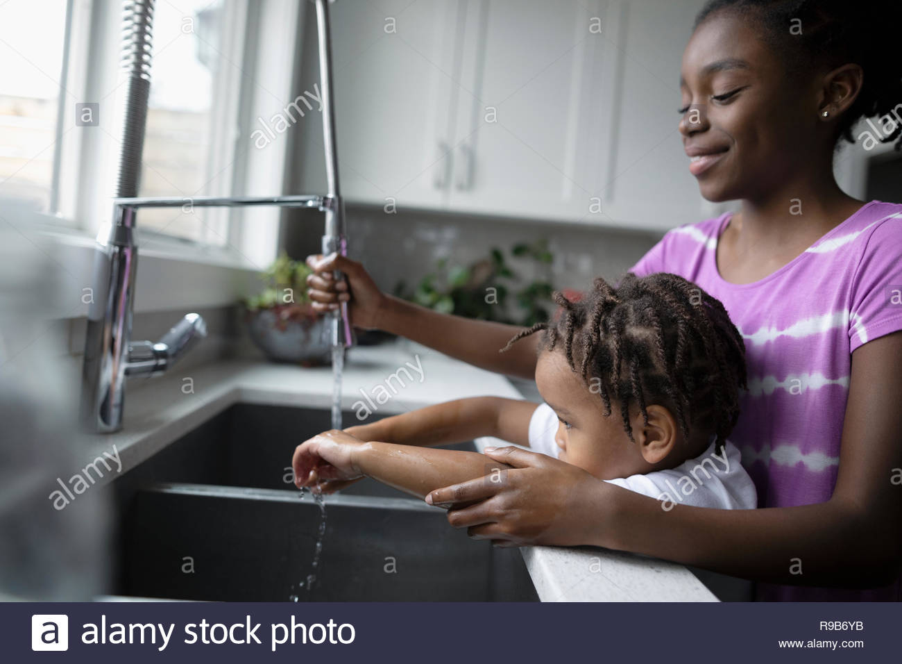 Sister helping toddler brother washing hands at kitchen sink Stock Photo