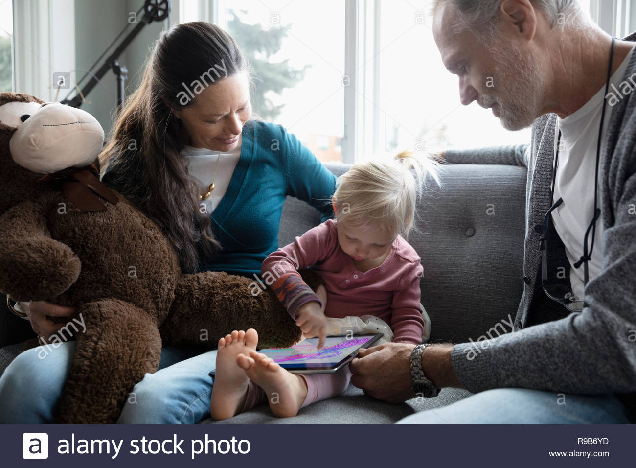 Grandparents watching granddaughter drawing on digital tablet Stock Photo