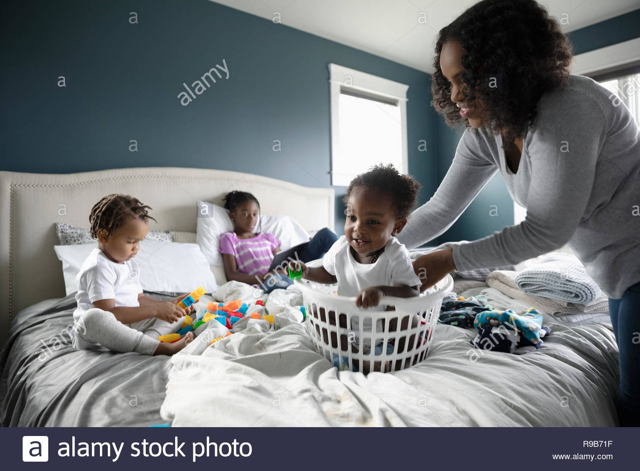 Playful mother placing baby son in laundry basket on bed - Stock Image