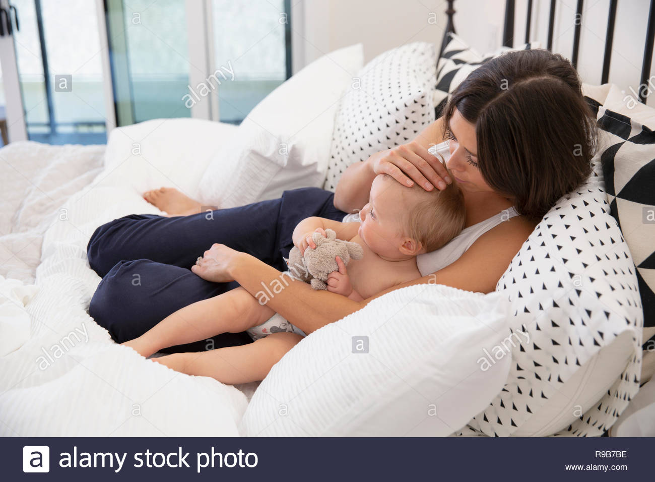 Affectionate mother and baby daughter relaxing on bed - Stock Image