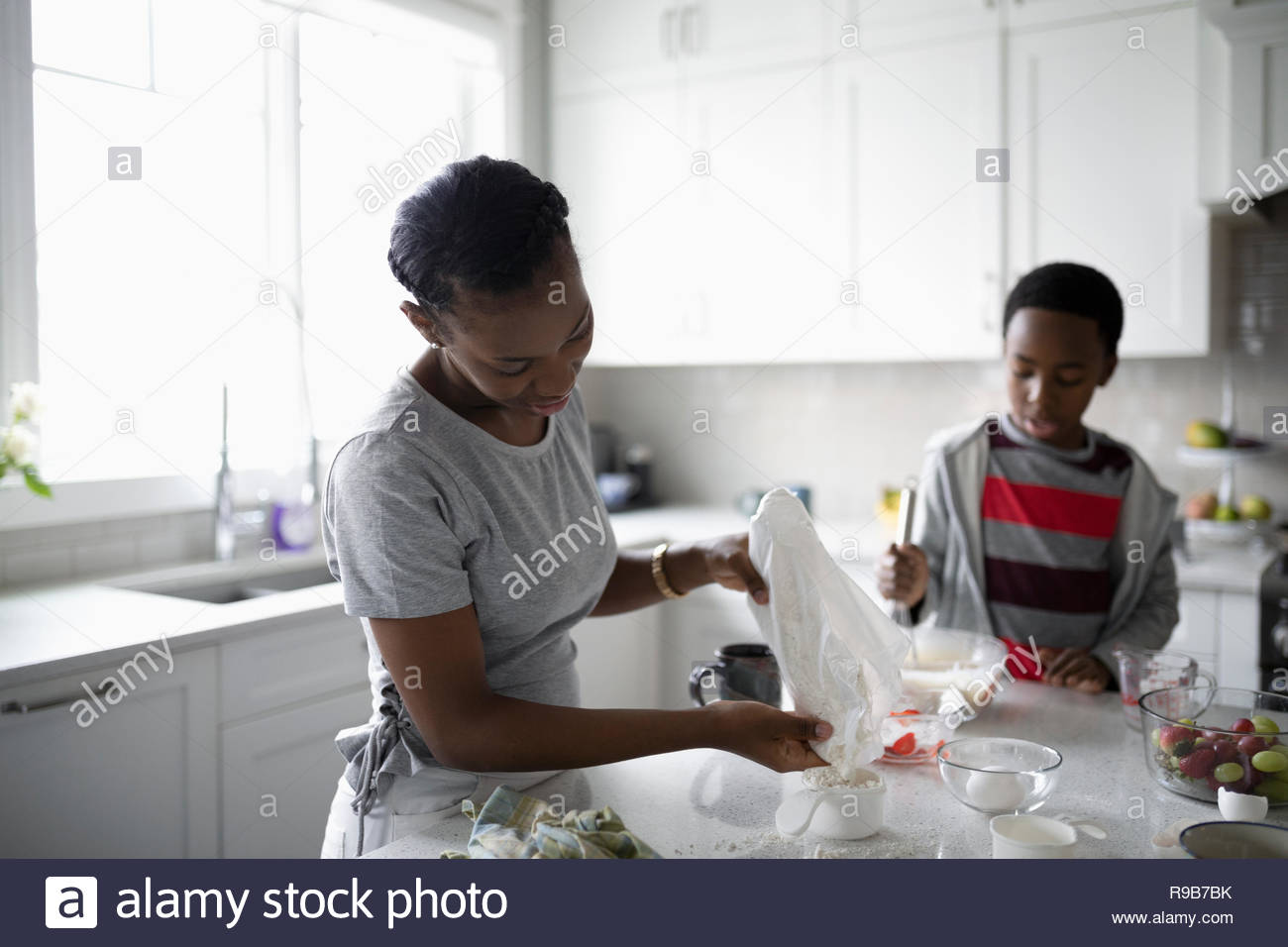 Mother and son baking in kitchen - Stock Image