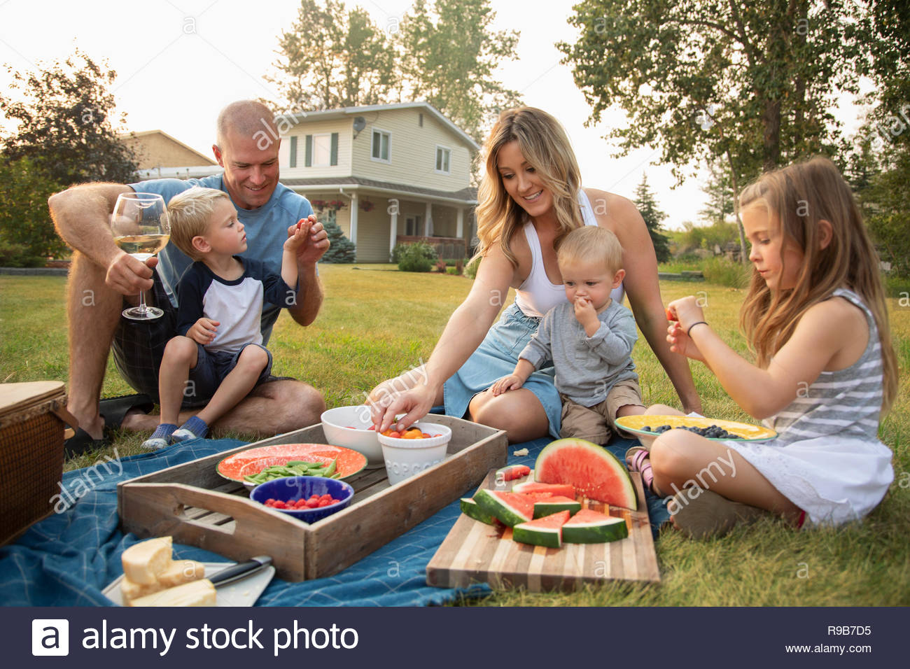 Young family enjoying picnic in rural yard - Stock Image