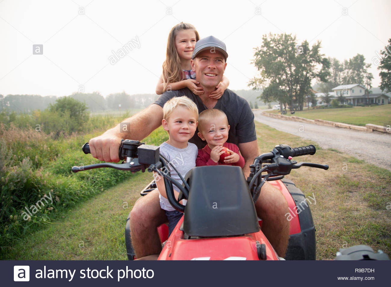 Father and young children riding quadbike on farm - Stock Image