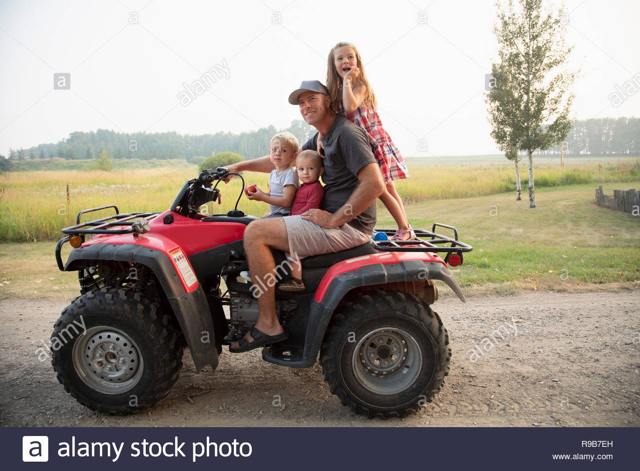 Portrait father and young children riding quadbike on farm - Stock Image