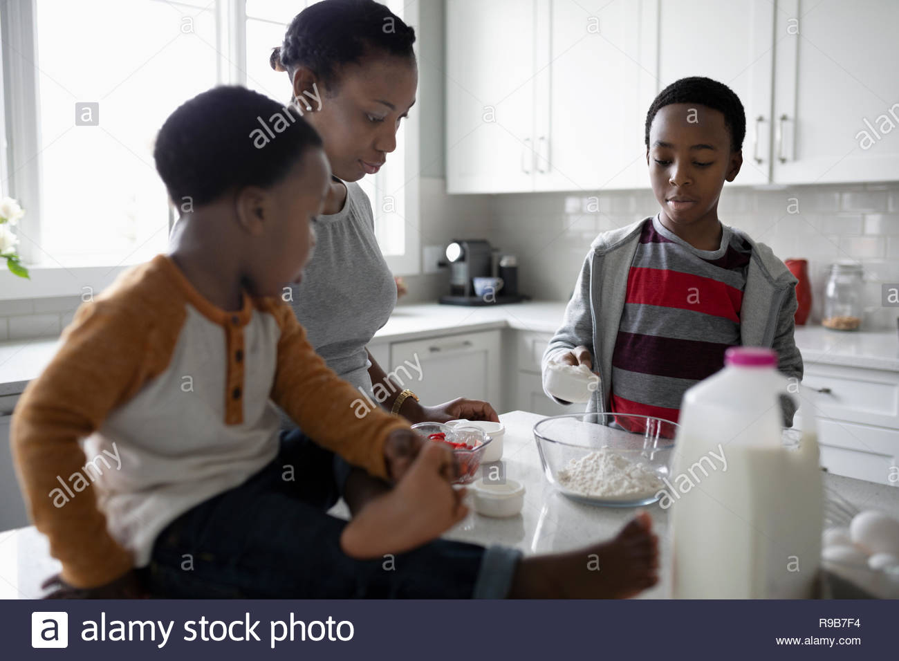 Mother and sons baking in kitchen - Stock Image