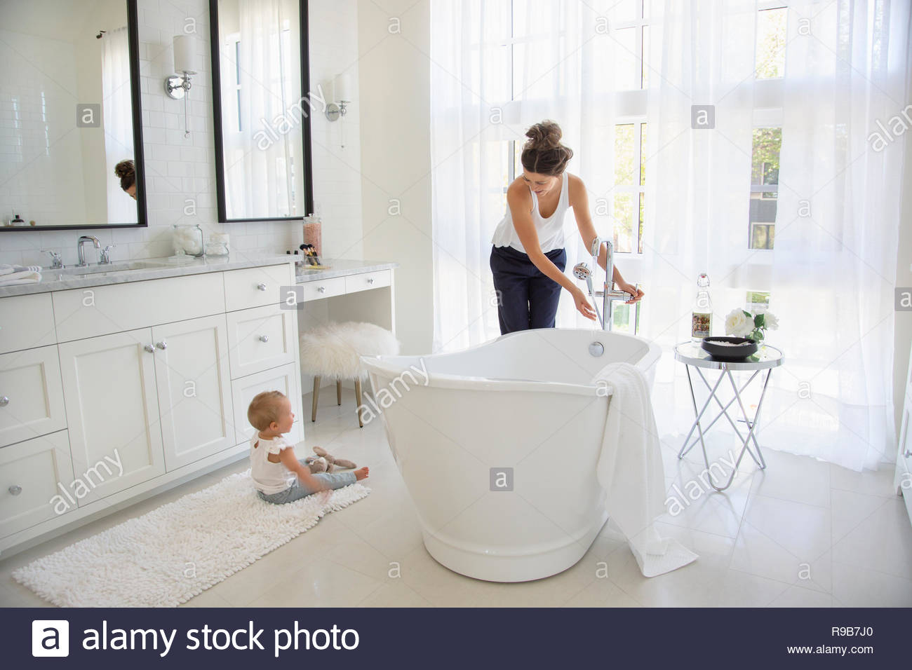 Mother and baby daughter preparing bath - Stock Image