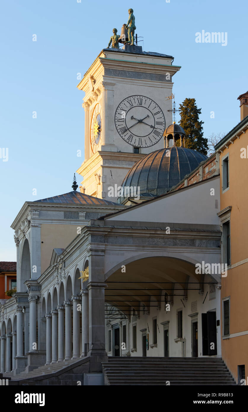 Loggia of Saint James and clock tower seen from Vittorio Veneto street at sunset in Libertà square in Udine, Italy - Stock Image