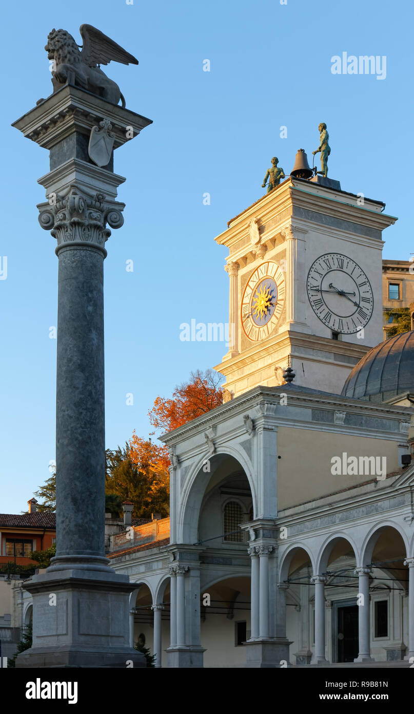 Loggia of Saint James, Saint Mark winged lion column and clock tower at sunset in Libertà square in Udine, Italy - Stock Image