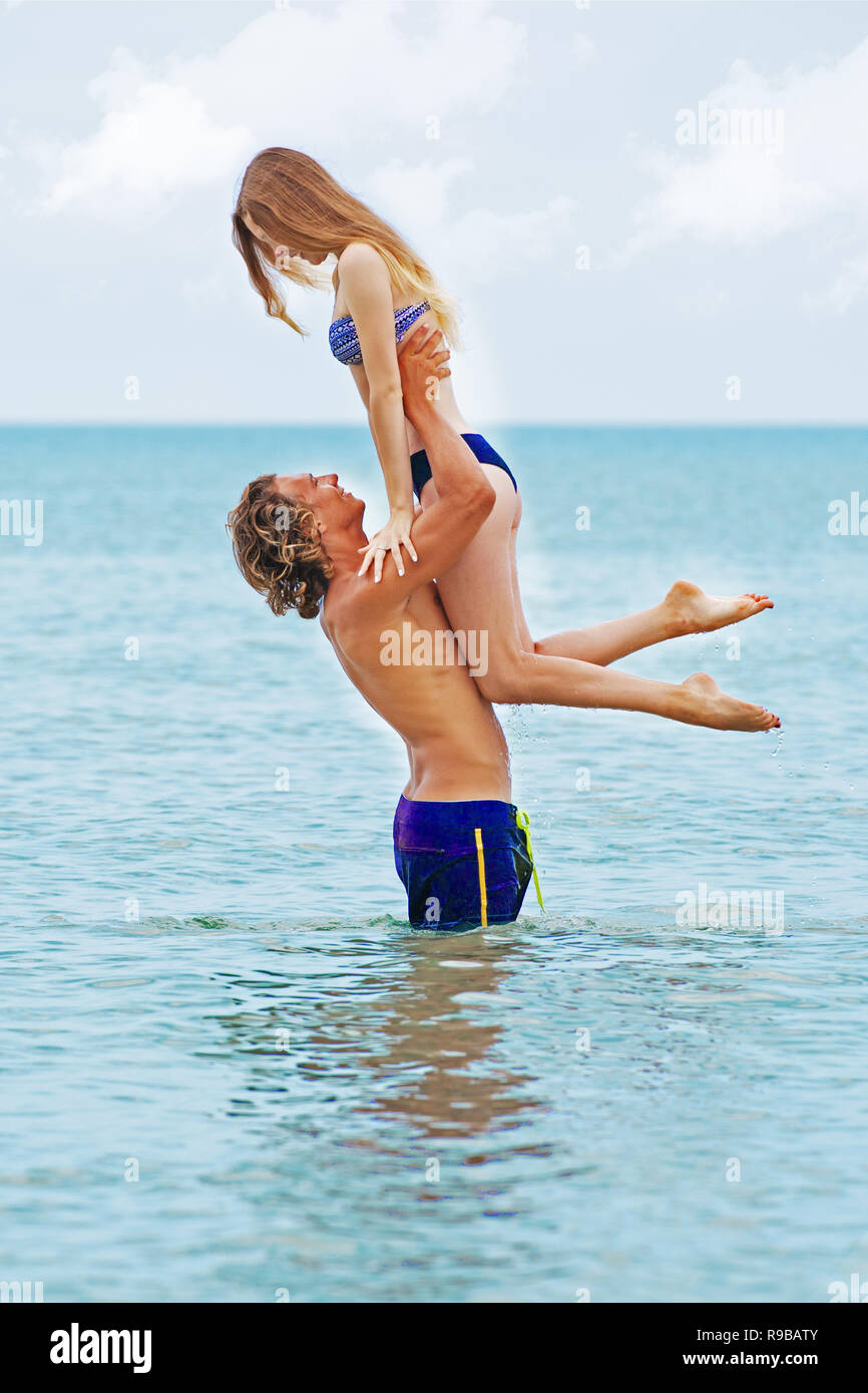 Woman jumps to the man in his arms, standing in the sea. Both are in the swimsuits. Smiling playful young couple in love having fun at sandy beach. - Stock Image